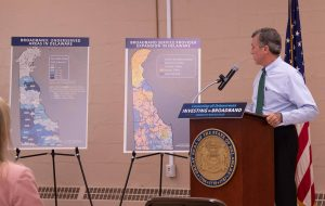 Governor Carney looks at service provider coverage maps while standing behind a podium.